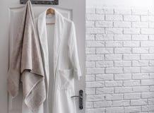 Hanger with clean towel and bathrobe. On door Stock Photo
