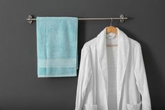 Hanger with clean towel and bathrobe. On grey wall Royalty Free Stock Images