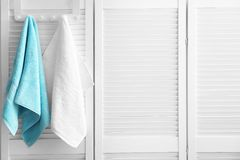 Hanger with clean towels. On folding screen Royalty Free Stock Image