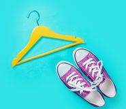 Hanger and gumshoes. On blue background Royalty Free Stock Images