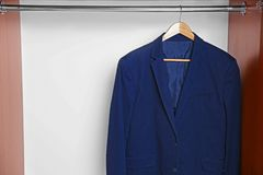 Hanger with male jacket on clothes rail. In wardrobe Stock Images