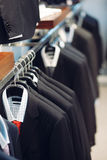 Hanger with men`s suits and shirts royalty free stock photography