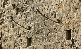 Hangers. Abstract architectural shot with a rubbed limestone facade and some metal hooks in Italy Royalty Free Stock Images