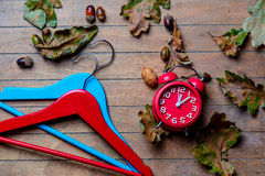 Hangers, alarm clock and fallen leaves Stock Photo