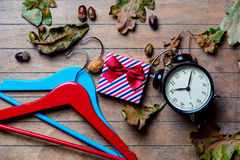 Hangers, alarm clock, gift and fallen leaves Royalty Free Stock Photography