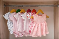 Hangers with baby clothes on rack. In wardrobe stock image