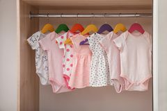 Hangers with baby clothes in wardrobe. Hangers with baby clothes on rack in wardrobe stock photos
