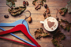 Hangers, cup of coffee and fallen leaves Stock Images