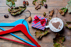 Hangers, cup of coffee, gift and fallen leaves Stock Photography