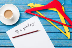 Hangers and cup of coffee near paper with inscription Stock Photos