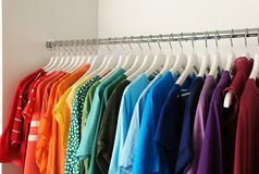 Hangers with different colorful clothes on rack. In wardrobe royalty free stock photography