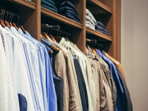 Hangers with different male clothes in store Royalty Free Stock Images