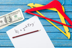 Hangers and dollars near paper with inscription Royalty Free Stock Images