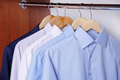 Hangers with male shirts on clothes rail. In wardrobe Royalty Free Stock Images