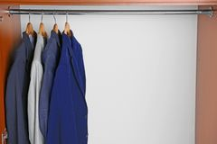 Hangers with male shirts on clothes rail. In wardrobe Stock Photo