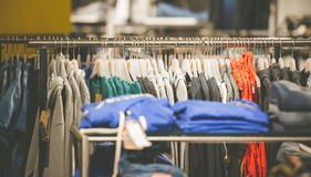 Hangers with men's clothes in shop Stock Photo