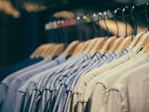 Hangers met verschillende mannelijke kleren in opslag stock foto