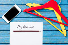 Hangers near paper with inscription and mobile phone Stock Image