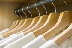 Hangers in a row with white shirts. On a gray bar in a wooden wardrobe stock photo