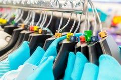 Hangers voor kleren in winkel met dimensionale tekens Stock Foto