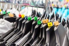 Hangers voor kleren in winkel met dimensionale tekens Royalty-vrije Stock Afbeelding