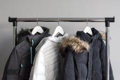 Hangertribune met warme jasjes De de winterjasjes met bontkraag hangen op witte houten hangers Inzameling van de winter stock afbeelding