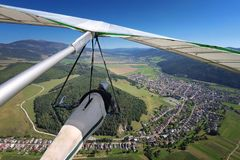 Hangglider pilot flies over small town in alpine valley Royalty Free Stock Photography
