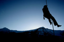 Hangin' out. A rock climber rappels into the twighlight royalty free stock photo