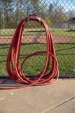 Hangin rouge de tuyau d'arrosage sur la barrière au terrain de base-ball image stock