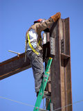 Hanging On. Construction worker climbing to the top of a steel beam high rise building project Stock Photography