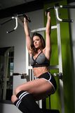 Hanging Abs Exercise Performing By A Woman. Attractive Woman Performing Hanging Leg Raises Exercise - One Of The Most Effective Abs Exercises Royalty Free Stock Photography