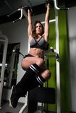 Hanging Abs Exercise Performing By A Woman. Attractive Woman Performing Hanging Leg Raises Exercise - One Of The Most Effective Abs Exercises Royalty Free Stock Image