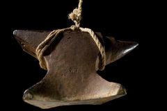 Hanging Anvil. An anvil hanging by a frayed rope and isolated on black Stock Image