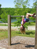 Hanging around. A young girl hangs upside down on a bar Stock Images