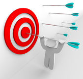 Hanging from Arrow in Target. A figure hangs from an arrow shot into a target's bullseye Royalty Free Stock Images