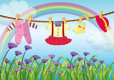 Hanging baby clothes near the garden with fresh flowers. Illustration of the hanging baby clothes near the garden with fresh flowers Royalty Free Stock Images