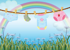 Hanging baby clothes under the rainbow Royalty Free Stock Photography