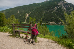 Hanging backpack and hiking shoes. Hiking path. Royalty Free Stock Image
