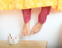 Hanging bare feet. Of a little girl - child under curtain over tabel with cup of tea Stock Image