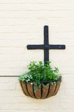 Hanging basket and the cross. Hanging basket on the white wall royalty free stock images