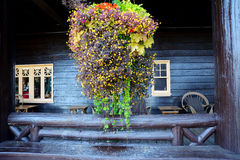 Hanging basket full of flowers hang before an old wooden hotel. Stock Photo