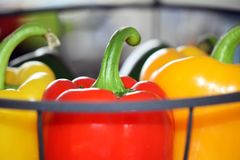 Some ripe and healthy sweet peppers with focus on the red one. Hanging basket with several sweet peppers with focus on the red one as symbol for healthy and Royalty Free Stock Photography