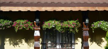 Hanging baskets of petunias cast shadows on house walls. Hanging baskets of purple and white petunias cast shadows om yellow wallso of house in Bucharest stock photography