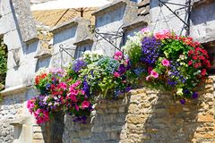Hanging baskets on pub wall, Castle Combe. Royalty Free Stock Photography