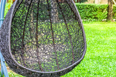 Hanging bench seat chair in basket design on the green grass field Stock Images