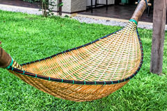 Hanging bench seat chair cradle hammock in basket design on the green grass field Royalty Free Stock Photos
