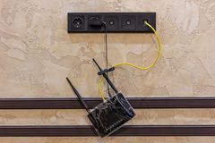 Hanging black internet router at home online stock image