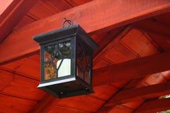 Hanging, black lantern on the wood