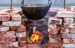Hanging black sooty cauldron over bonfire surrounded by a brick wall, camping vacation outdoor kitchen. Hanging big black sooty cauldron over bonfire surrounded royalty free stock photos
