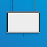 Hanging blank projector screen empty conference display on blue Stock Photography